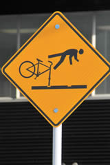 Sign Showing Person Falling off a Bike After Going Down Tram Lines