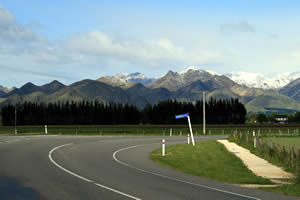 South Island road in New Zealand with mountain range in background.
