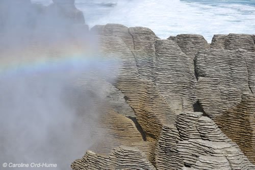 Punakaiki Pancake Rocks Blowhole at high tide with a Rainbow across the blowhole caused by the water spray. South Island West Coast, Paparoa National Park New Zealand