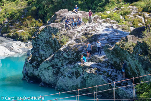 Visitors to Hokitika Gorge sitting on the rocks by the side of the river in the sun, West Coast, New Zealand